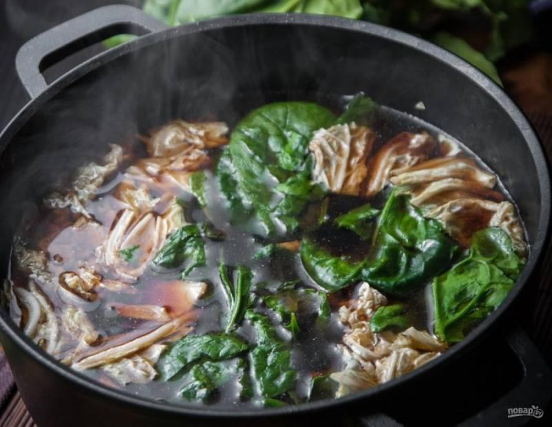 Затем добавьте лапшу. В самом конце добавьте шпинат и пекинскую капусту, нарвав их.