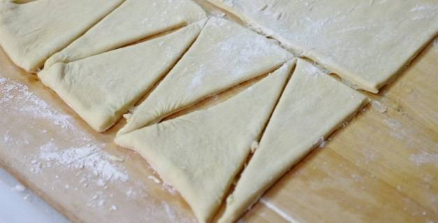 1. Этот рецепт приготовления пальчиков с сыром - пример вкусной выпечки на скорую руку. Заранее тесто нужно немного разморозить, а затем раскатать на присыпанной мукой поверхности. Аккуратно нарежьте его треугольниками одинакового размера. Если под рукой окажется специальное тесто для круассанов и пальчиков, тогда это еще и сэкономит время для раскатки.