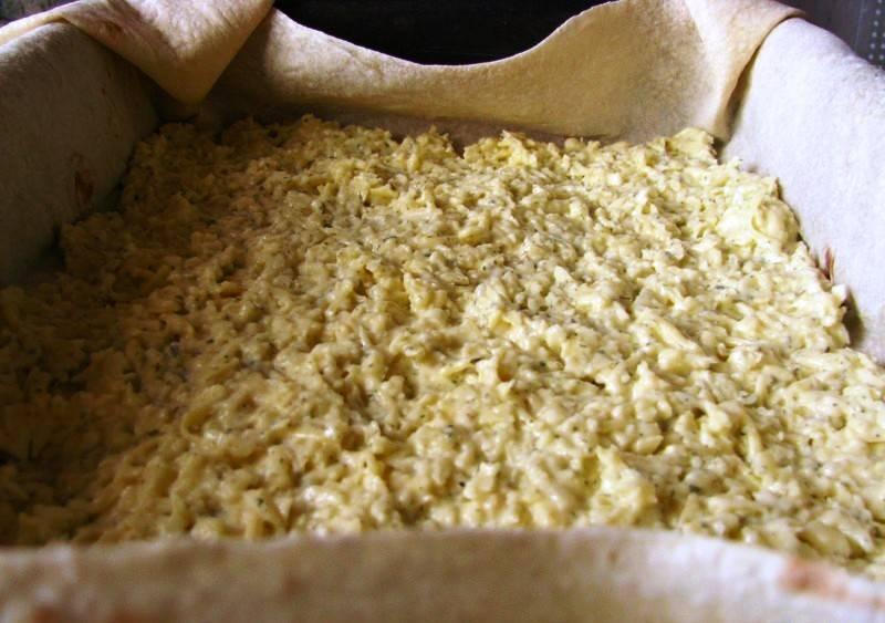 Форму смажьте маслом, выложите в неё лаваш. Распределите тонким слоем часть начинки.