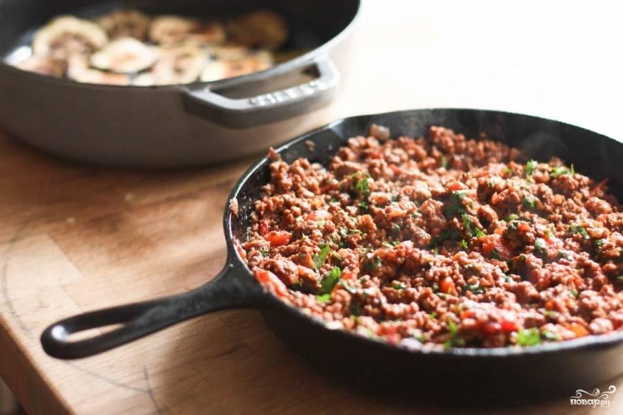 Теперь приготовим фарш. На сковороде обжарьте мелко рубленный лук на среднем огне, 3-4 минуты. Добавьте нарезанный чеснок (можете выдавить) и жарьте чеснок с луком ещё 8-10 минут. Лук станет мягким. Затем к луку и чесноку выложите бараний фарш. Тушите всё вместе 15 минут. Фарш должен стать коричневым. Вылейте лишний жир из сковороды столовой ложкой. Добавьте белое вино, нарезанные на маленькие кусочки помидоры, томатную пасту, рубленную петрушку, сахар, корицу. Посолите и поперчите. Тушите всё на среднем огне 20 минут.