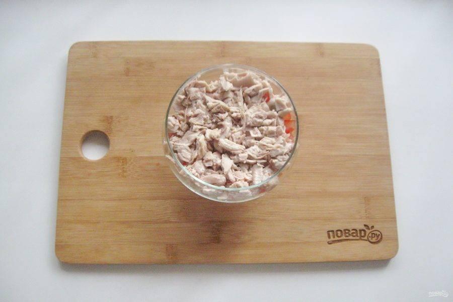 Второй слой — отварная курица. Мелко нарежьте и выложите на помидор. Смажьте майонезом.