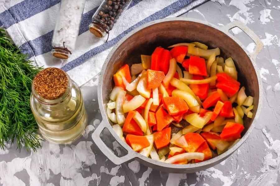 Морковь очистите от кожуры, промойте в воде и нарежьте средними ломтиками, а половину репчатого лука - полукольцами. Влейте в казан или ковш с антипригарным покрытием растительное масло. Раскалите его и выложите в него овощные нарезки. Убавьте нагрев до среднего и обжарьте около 2-3 минут, периодически перемешивая.