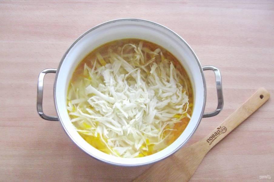 Когда картофель, лук и морковь будут на стадии полуготовности, выложите в щи нарезанную капусту.