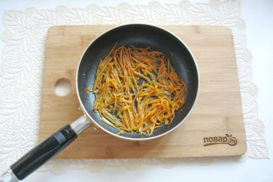 Налейте немного подсолнечного масла и тушите морковь 7-8 минут, периодически перемешивая.