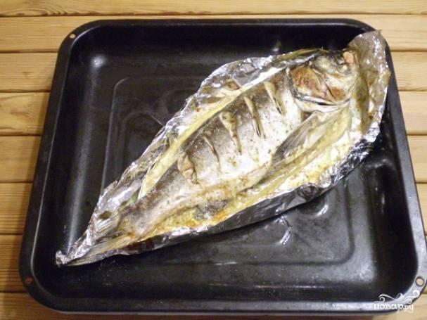 Спустя 30 минут осторожно раскройте фольгу и зарумяньте рыбку.