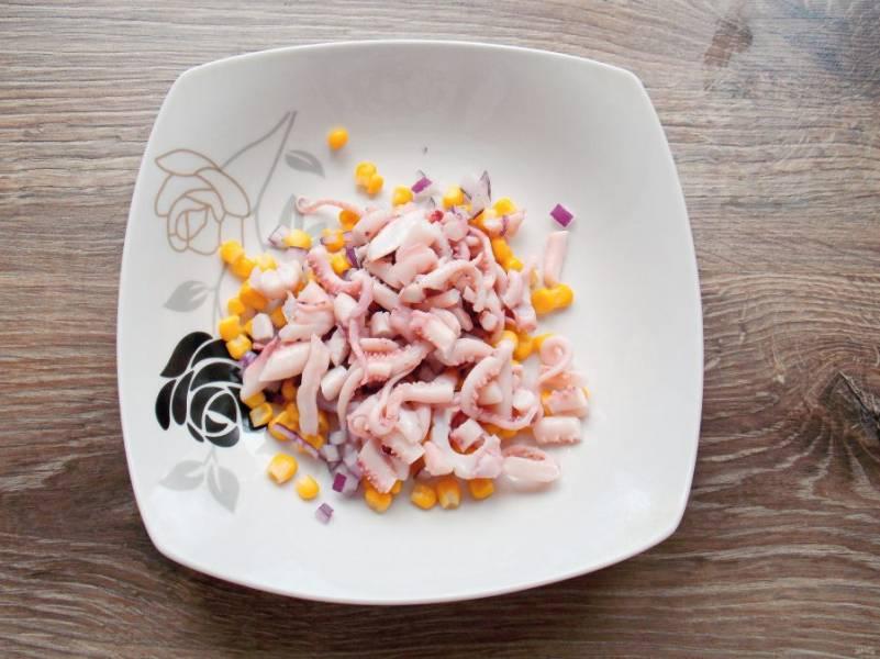 Щупальцы кальмара извлеките из масла и порежьте на кусочки. Добавьте их в салатник с овощами.