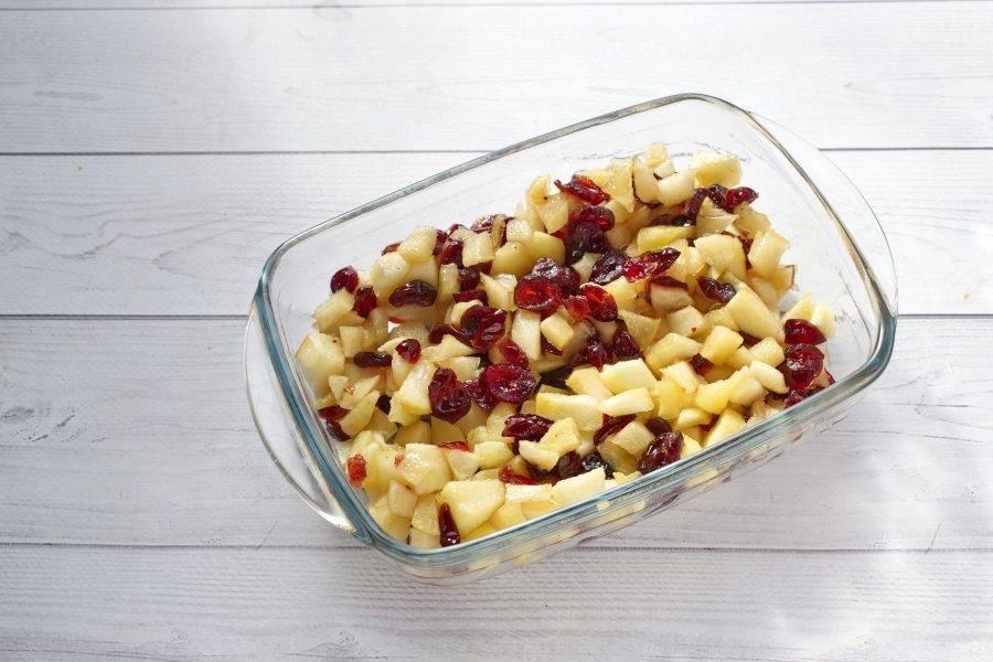 Яблоки и клюкву разместите по дну формы для запекания.