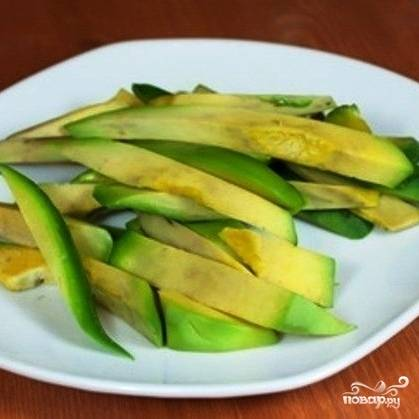 На аналогичные полоски нарезаем очищенный от кожуры и косточки авокадо.