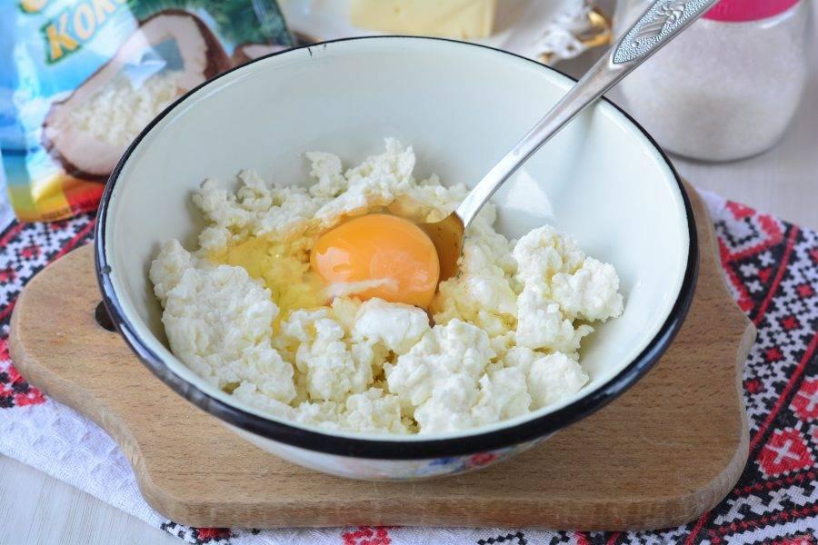Всыпьте творог в миску, вбейте одно крупное яйцо, перемешайте.