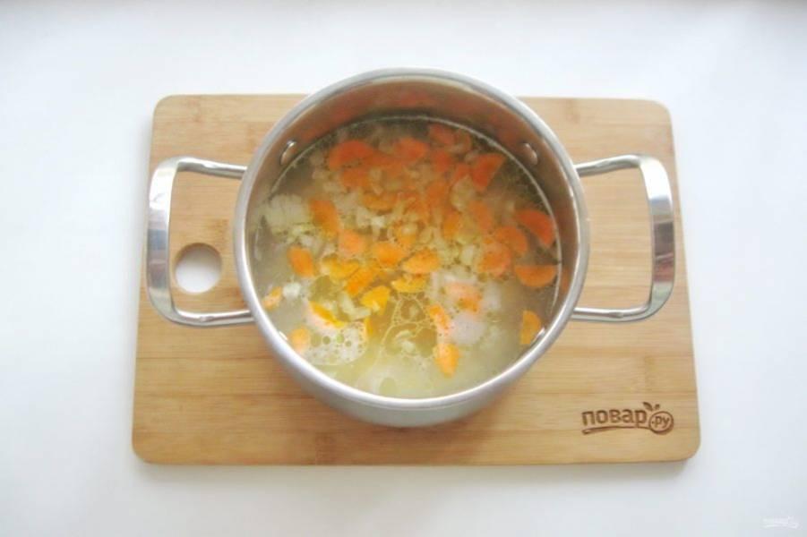Затем выложите морковь и лук в кастрюлю с картофелем и бульоном.
