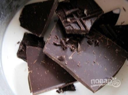 Пока печется бисквит, сделайте шоколадный ганаш. В кастрюльку влейте остаток сливок и добавьте к ним поломанный руками черный шоколад. Поставьте кастрюльку на огонь и подождите, пока шоколад растает.