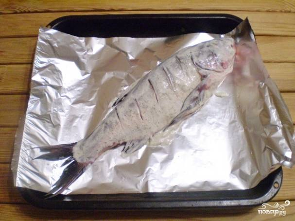 Уложите рыбу на фольгу. Сделайте надрезы.