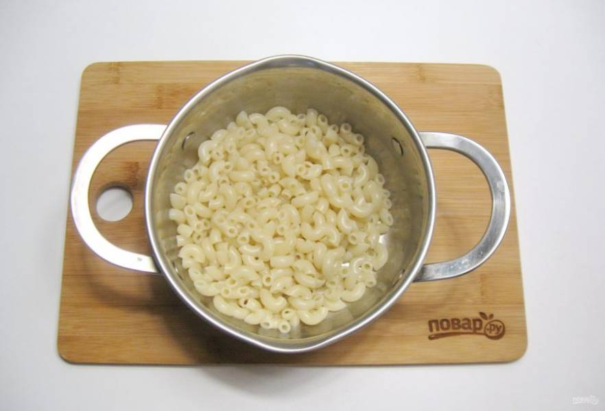 Отварите макароны. Для этого в кипящую, подсоленную воду выложите макароны, перемешайте, чтобы они не прилипли ко дну. Варите 10-12 минут. После воду слейте.