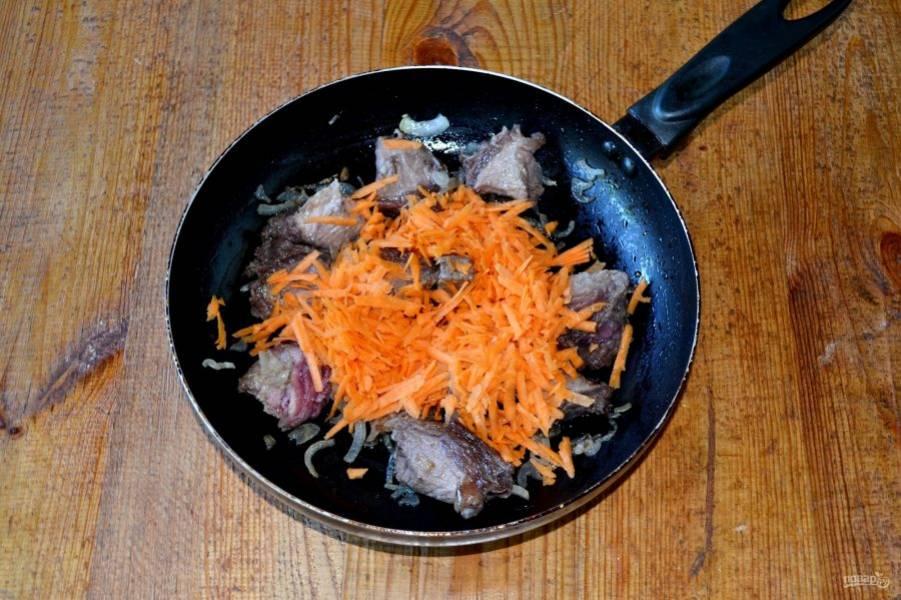 После добавьте морковь, снизьте огонь до среднего и жарьте еще 2-3 минуты. За это время перетрите помидоры.