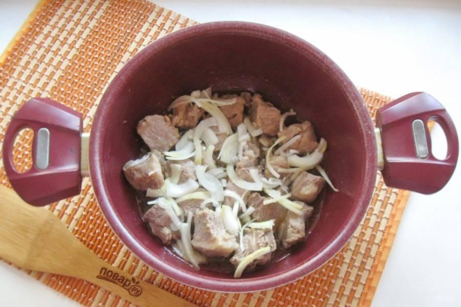 Одну крупную луковицу очистите, помойте и нарежьте. Добавьте в кастрюлю с мясом и обжарьте под крышкой в течение 5-6 минут, перемешайте.