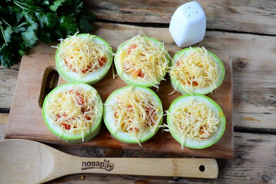 Помидор мелко нарежьте. В каждое углубление положите по 1 ч. ложке помидоров, присыпьте тертым сыром. Положите заготовки на пергамент и отправьте в духовку на 20 минут.