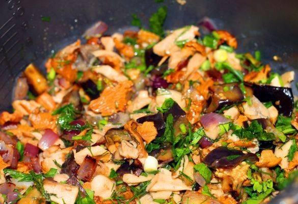 Смешать обжаренные грибы и баклажаны, добавить к ним нарезанную зелень. Накрыть сковороду крышкой и тушить минут 15. Можно потушить в духовке.