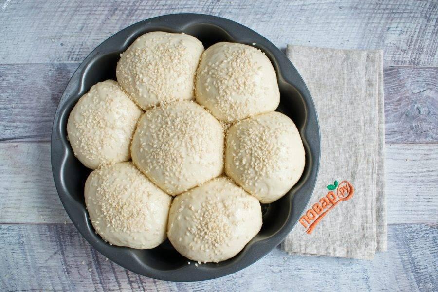 Подошедшие булочки смажьте слегка взбитым белком, посыпьте кунжутом. Поставьте в разогретую духовку на 35-40 минут, выпекайте при 200 градусах.