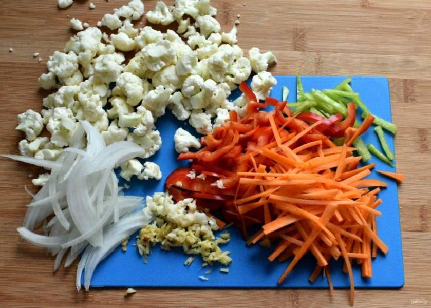 Разберите цветную капусту на мелкие соцветия, морковь и перец нашинкуйте соломкой, репчатый лук тонко нарежьте вдоль луковицы. Чеснок и имбирь мелко порубите.