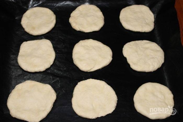 4.Противень смажьте маслом и разложите маленькие основы для пиццы, придав им форму просто руками.