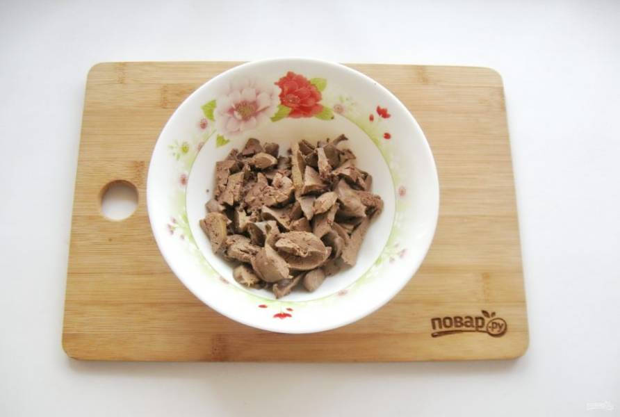 Нарежьте отварную куриную печенку и выложите в салатник.