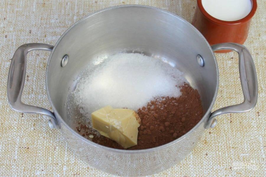 Подготовим глазурь. В кастрюлю высыпаем оставшийся сахар, какао и кладем кусочек какао-масла.