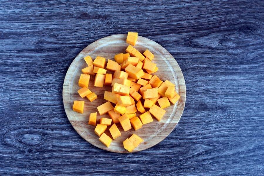 Вскипятите 1,5 литра воды. Тыкву нарежьте кубиками среднего размера и опустите в кипяток. Варите 2 минуты.