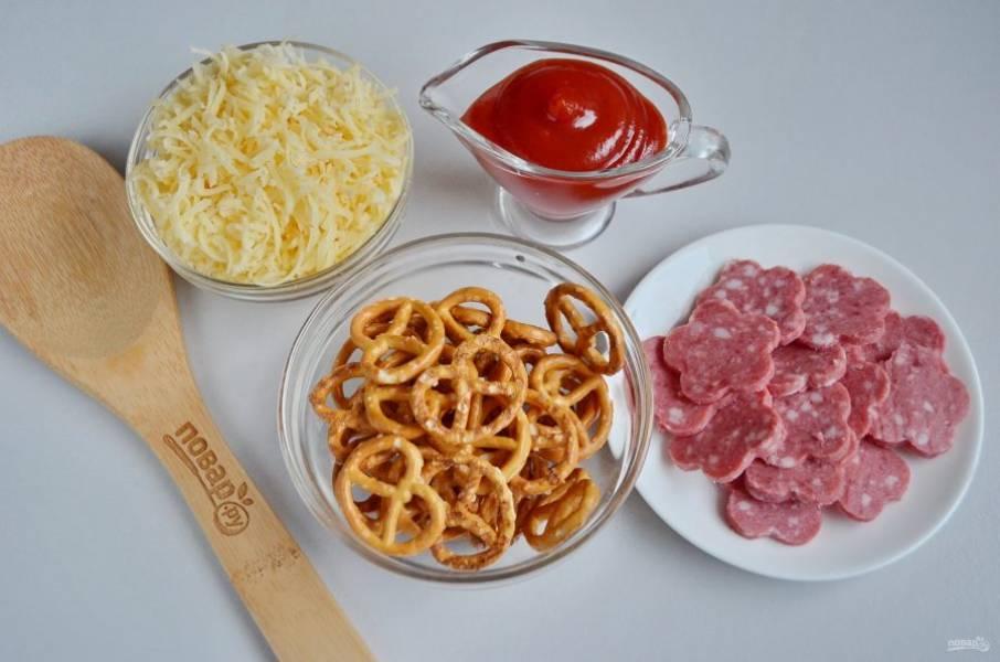 Подготовьте продукты. Колбасу тонко порежьте, она должна быть не больше самого кренделька. Сыр натрите на мелкой терке. Приступим!