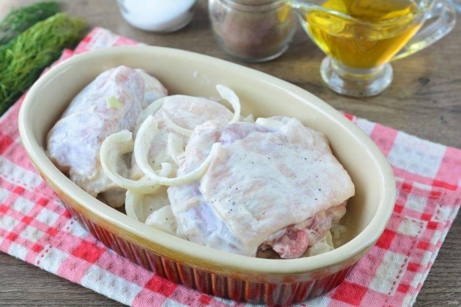 Форму для запекания смажьте маслом, выложите куриное мясо с луком и майонезом, разровняйте.