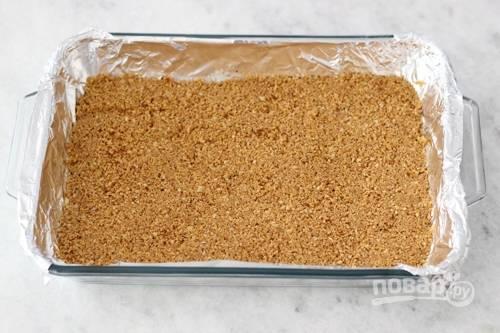 2. Подготовьте жаропрочную форму, застелив ее фольгой или пергаментом. Выложите крошку и плотно прижмите руками. Отправьте в разогретую до 180 градусов духовку минут на 15.