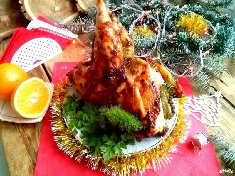 Запекайте в разогретой духовке 30 минут, затем снизьте температуру до 180 градусов и запекайте птицу до готовности, примерно около 1-1,5 часа. Во время запекания смажьте птицу пару раз фруктовым соусом.  Время запекания зависит от возраста птицы и жесткости мяса. Чтобы узнать, когда мясо готово, проткните его зубочисткой. Если выделившийся сок прозрачный, петух готов. Немного остудите его и подавайте к столу.