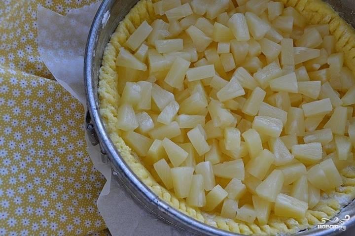 Слейте с консервированного ананаса воду, выложите затем кусочки фруктов на тесто, равномерно распределив их по всей поверхности пирога.