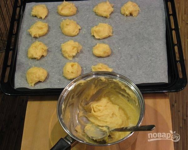 Противень застелите бумагой для выпечки. Смажьте её маслом. Выложите тесто в виде профитролей на противень.