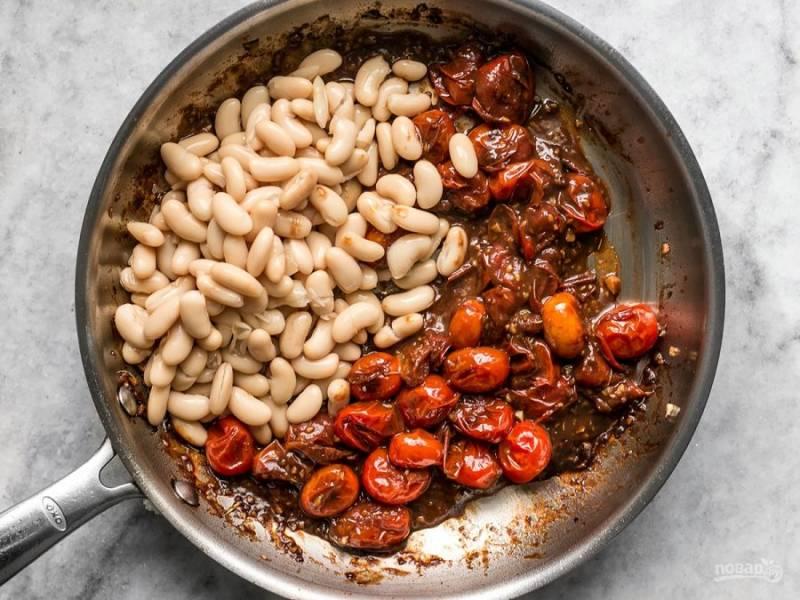 4.Слейте воду с консервированной фасоли и выложите в сковороду. Тем временем отправьте хлеб в духовку, чтобы он поджарился.