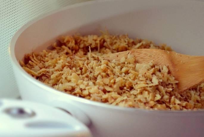 Теперь высыпаем измельченные орехи в кастрюльку с толстым дном или в сковороду и обжариваем их без добавления масла, периодически помешивая. Жарить нужно примерно 10-12 минут.