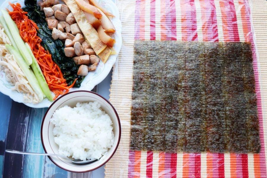 Всю подготовленную начинку выложите на тарелку. Циновку для сворачивания роллов затяните пищевой пленкой и положите на нее лист нори.