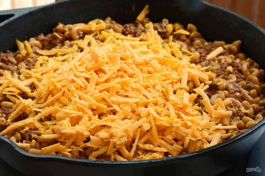 8.Натрите на терке сыр, снимите крышку и добавьте его в сковороду.