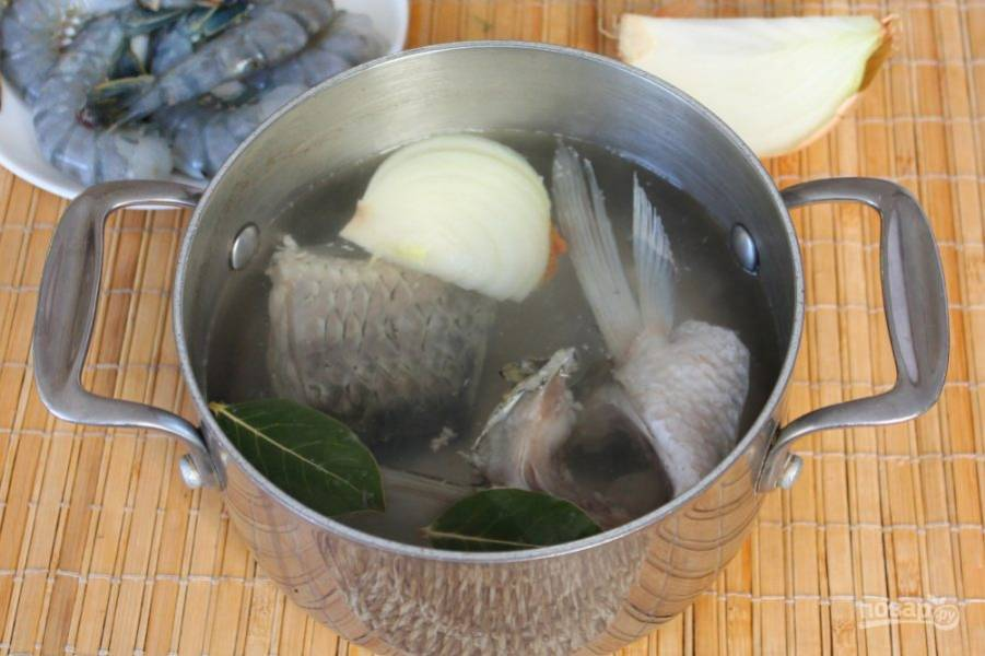 Рыбу чистим, потрошим и промываем холодной водой. Куски белого амура кладем в кастрюлю и заливаем водой. Доводим до кипения и убираем пену. Далее, добавляем соль,  лавровый лист и часть луковицы. Варим рыбный бульон. Через 15 минут лук и лавровый лист убираем.