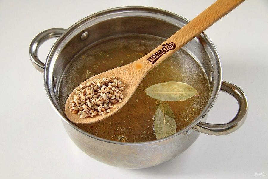 Доведите бульон до кипения. Добавьте соль, специи, лавровый лист и перловую крупу. Готовьте после закипания на небольшом огне около 40 минут или до тех пор, пока крупа не станет мягкой.