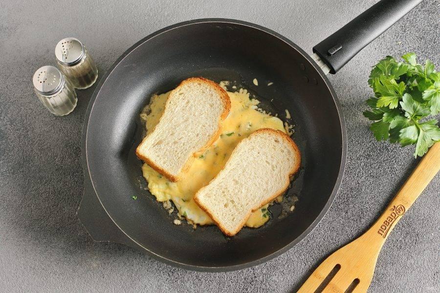 Сверху выложите два кусочка хлеба. Рядом друг с другом, но на некотором расстоянии друг от друга. Прижмите хлеб лопаткой и дайте сыру расплавиться.