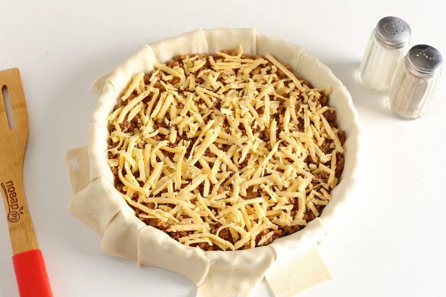 Посыпьте фарш тертым сыром.