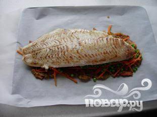 Положить пищевую бумагу на противень, примерно в три раза шире чем рыба.  Выложить слой лука, потом моркови и гороха.   Рыба сверху.