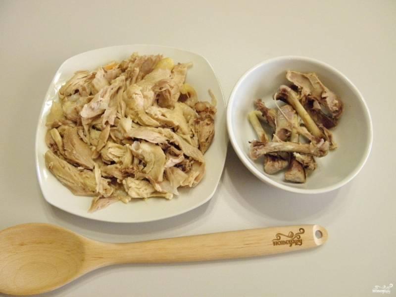 Достаньте мясо и отделите его от костей. с помощью двух вилочек это легко можно сделать. Порвите мясо на кусочки. Верните в бульон.