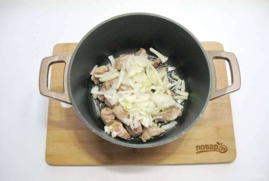Репчатый лук очистите, помойте и нарежьте полукольцами. Добавьте в кастрюлю с мясом.