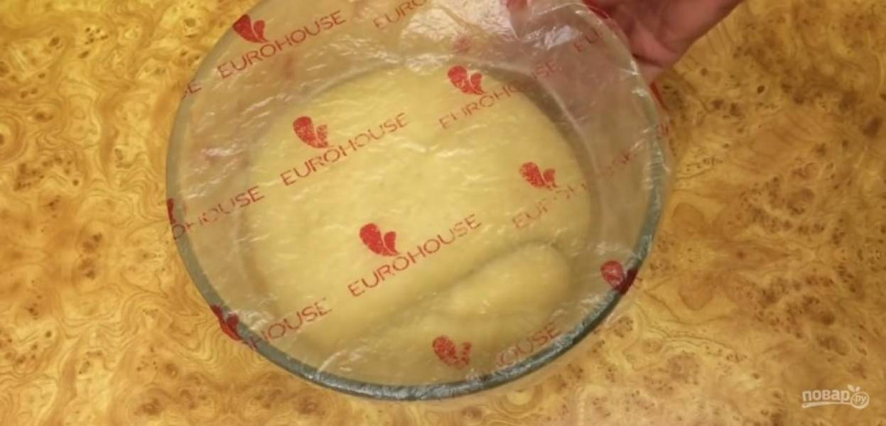 4.  Замесите тесто еще в течение 7-10 минут. Округлите тесто, выложите в смазанную растительным маслом миску и накройте пленкой. Оставьте при комнатной температуре на 4 часа. Сложите тесто: руками растяните в прямоугольник.