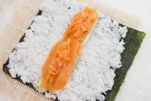 Оберните бамбуковый коврик в пакет. Выложите лист нори и сверху выложите тонкий слой риса, оставляя 1-2 см с одного краю. Выложите огурец и лосось.