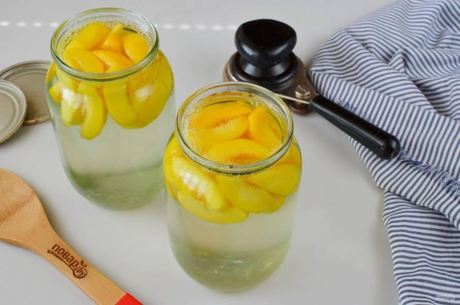 Залейте кипящим компотом персики, закатайте крышками банки.