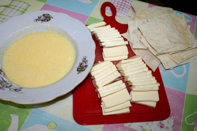 2. Также нужно нарезать тонкими пластинками сыр. При желании в рецепт приготовления конвертов из лаваша с сыром можно использовать бутербродный плавленый сырок с различными добавками. Для кляра необходимо взбить в небольшой мисочке яйца, добавить соль по вкусу и крахмал.
