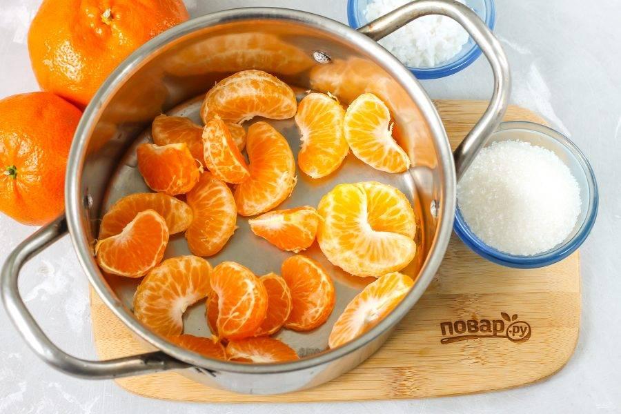 Мандарины очистите от кожуры и белого слоя под ней. Разделите плоды на дольки и выложите их в кастрюлю, казан или ковш.