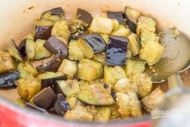 1. Баклажан нарежьте кубиками. Обжарьте их в глубокой сковороде или кастрюле в масле в течение 10 минут. Немного добавьте соли.